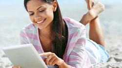 Lady-on-beach-reading-tablet-250x139